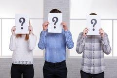 Zwei Kerle und ein Mädchenstand schließen nebeneinander ihre Gesichter mit Blättern mit Fragezeichennahaufnahme Lizenzfreie Stockbilder