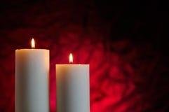 Zwei Kerzen mit rotem Hintergrund stockbilder