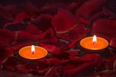 Zwei Kerzen und rote rosafarbene Blumenblätter stockfotografie