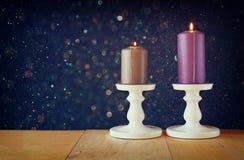 Zwei Kerzenständer mit brennenden Kerzen über Holztisch- und Weinlesefunkelnhintergrund Lizenzfreie Stockbilder