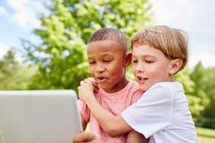 Zwei Kinder als Freunde mit Laptop stockfotos