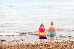 Zwei Kinder auf dem Strand, der Meer betrachtet Stockfotos