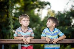 Zwei Kinder auf dem Wandern, dem Stand und dem Blick auf den Horizont umgeben durch warme sonnige Farben Konzept der Freundschaft stockbilder