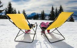 Zwei Kinder auf den Klubsesseln auf Schnee stockfoto