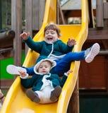 Zwei Kinder auf Dia am Spielplatz Stockfotos