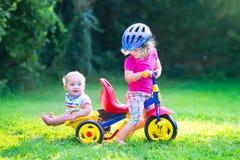 Zwei Kinder auf einem Fahrrad im Garten Lizenzfreies Stockfoto
