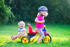 Zwei Kinder auf einem Fahrrad im Garten Stockfotos