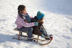 Zwei Kinder auf einem Schlitten, der Spaß hat   Stockfotos
