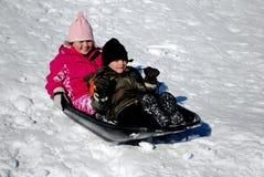 Zwei Kinder auf einem Schneeschlitten Stockbilder