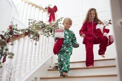 Zwei Kinder auf Treppe in den Pyjamas mit Weihnachtsstrümpfen Stockbilder
