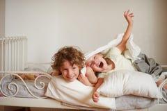 Zwei Kinder, Bruder und Schwester, geben sich auf dem Bett im Schlafzimmer hin Lizenzfreie Stockfotos