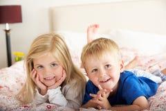 Zwei Kinder, die auf Bett sich entspannen stockfotos