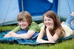 Zwei Kinder, die auf Decke mit Zelt im Hintergrund liegen Stockfotos