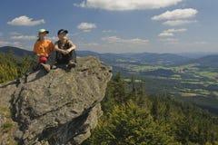 Zwei Kinder, die auf einem Felsen in den Bergen sitzen Stockfoto