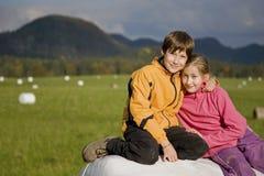 Zwei Kinder, die auf einem Heuballen sitzen Lizenzfreie Stockbilder