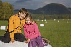 Zwei Kinder, die auf einem Heuballen sitzen Lizenzfreie Stockfotos
