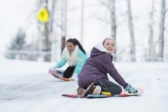Zwei Kinder, die auf einem Schneeschlitten im Winter spielen Stockbilder