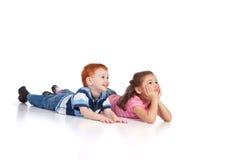 Zwei Kinder, die auf Fußboden liegen Lizenzfreie Stockfotos