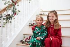 Zwei Kinder, die auf Treppe in den Pyjamas am Weihnachten sitzen Stockfoto