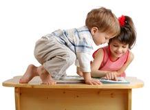 Zwei Kinder, die das Buch auf dem Schreibtisch lesen Lizenzfreie Stockfotos
