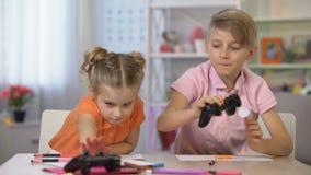 Zwei Kinder, die das Zeichnen beenden, Steuerknüppel nehmend von der Tabelle, Videospielfreizeit stock video footage