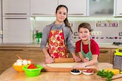 Zwei Kinder, die den Teig für die Herstellung der Pizza kneten Stockbild