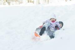 Zwei Kinder, die draußen hinunter schneebedeckten Hügel auf orange modernen Plastiktoboggan für Kinder schieben Stockfotografie