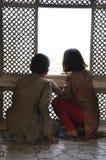 Zwei Kinder, die durch ein Fenster aufpassen Lizenzfreies Stockbild