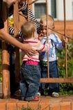 Zwei Kinder, die durch Zaun spielen Stockbilder