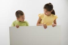 Zwei Kinder, die ein unbelegtes Zeichen anhalten Stockbild