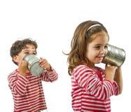 Zwei Kinder, die an einem Zinntelefon sprechen Stockbild