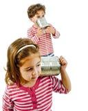 Zwei Kinder, die an einem Zinntelefon sprechen Stockfotos