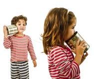 Zwei Kinder, die an einem Zinntelefon sprechen Stockfoto