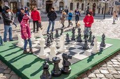 Zwei Kinder, die in enormen beweglichen Schachfiguren auf dem Brett am zentralen Marktplatz in Lemberg spielen, Leute betrachten  Lizenzfreie Stockbilder