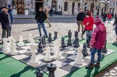 Zwei Kinder, die in enormen beweglichen Schachfiguren auf dem Brett am zentralen Marktplatz in Lemberg spielen, Leute betrachten  Stockbilder