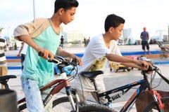 Zwei Kinder, die Fahrräder auf dem Strand spielen stockfotos