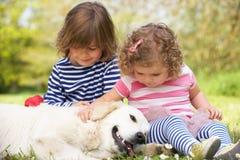 Zwei Kinder, die Familien-Hund auf dem Sommer-Gebiet Petting sind stockfotos