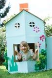 Zwei Kinder, die im gemachten Papphaupthaus spielen Stockbilder