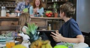 Zwei Kinder, die im Küchen-Uhr-lustigen Video zusammen spricht mit Mutter und Vater Cooking, glückliche Familie zu Hause sitzen stock video