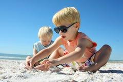Zwei Kinder, die im Sand am Strand spielen stockfotografie