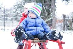Zwei Kinder, die im Winter rodeln Lizenzfreie Stockfotos