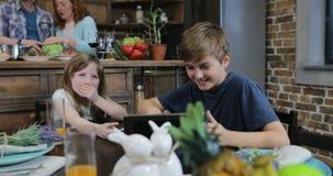 Zwei Kinder, die am Küchentisch-Uhr-lustigen Video während Mutter und Vater Cooking, glückliche Familie zusammen zu Hause sitzen stock footage