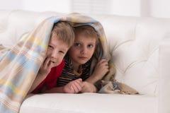 Zwei Kinder, die Kamera unter Decke untersuchen Stockbild