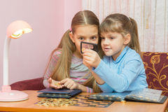 Zwei Kinder, die Münze durch eine Lupe betrachten stockfoto