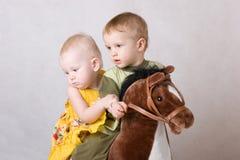 Zwei Kinder, die mit einem Spielzeugpferd spielen Stockbilder