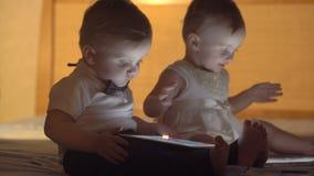 Zwei Kinder, die mit einer Tablette spielen stock footage