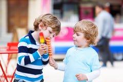 Zwei Kinder, die mit Eiscreme sich einziehen Stockbild