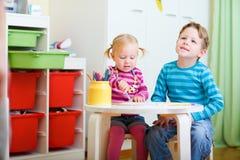 Zwei Kinder, die mit Farbtonbleistiften zeichnen Lizenzfreie Stockbilder