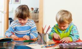 Zwei Kinder, die mit Papier und Bleistiften spielen Stockfotografie