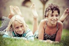Zwei Kinder, die oben auf Gras liegen stockbilder
